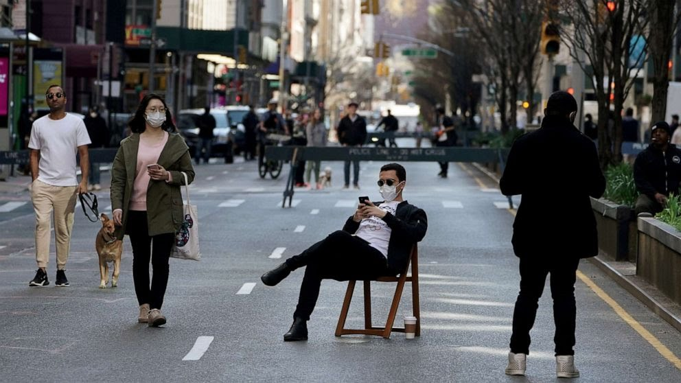 FILE PHOTO: A man sits on a chair as people walk on Park Avenue that was closed to vehicular traffic during the outbreak of coronavirus disease (COVID-19), in the Manhattan borough of New York City, New York, U.S., March 27, 2020. Carlo Allegri/Reuters